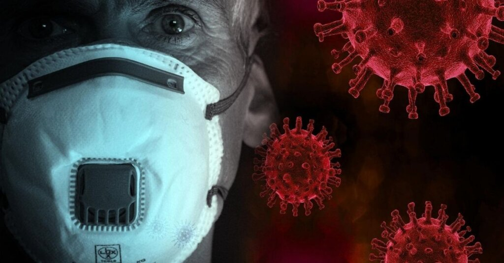A man wearing a mask surrounded by cartoon virus molecules