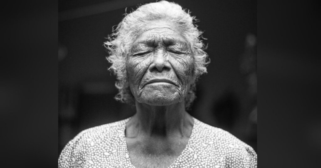 Elderly woman with her eyes closed