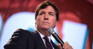 Tucker Carlson holding a microphone