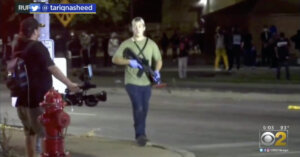 Kyle Rittenhouse walks through the streets of Kenosha proudly carrying an automatic rifle.