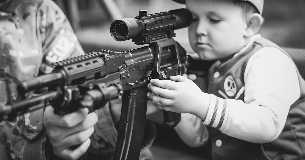 A child learns how to aim an automatic rifle.