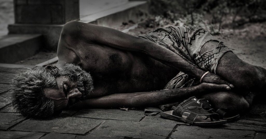 A starving man lies on the pavement
