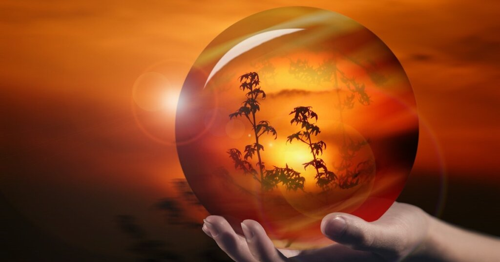 Peering through a crystal ball at a firey landscape.
