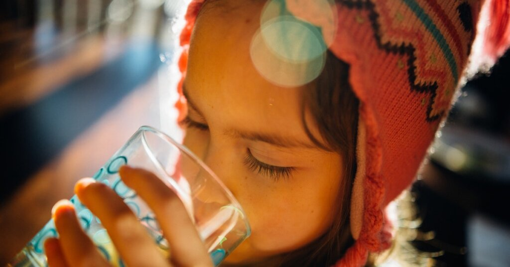 A child drinks from a water glass.