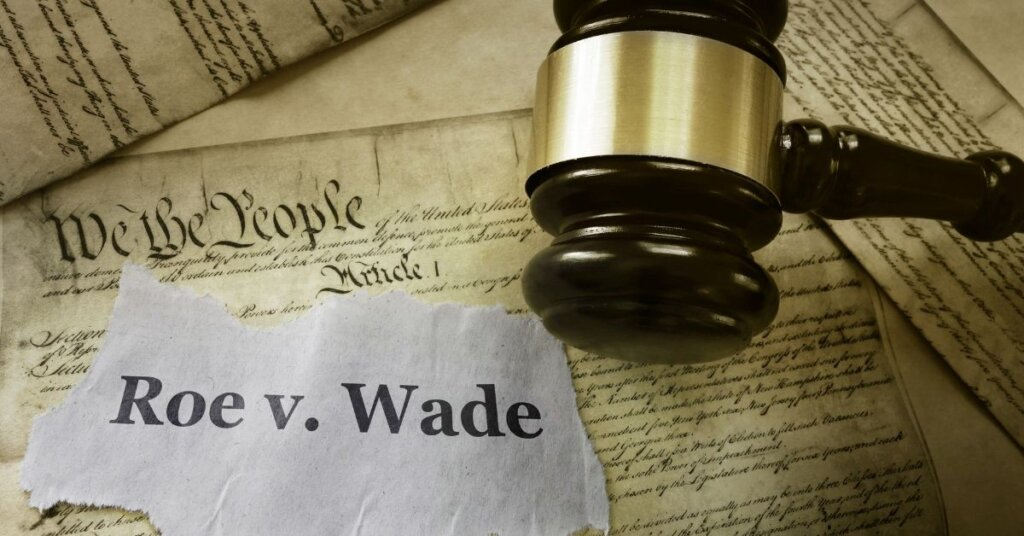 A gavel and a slip of paper that says Roe vs Wade lying on top of the constitution