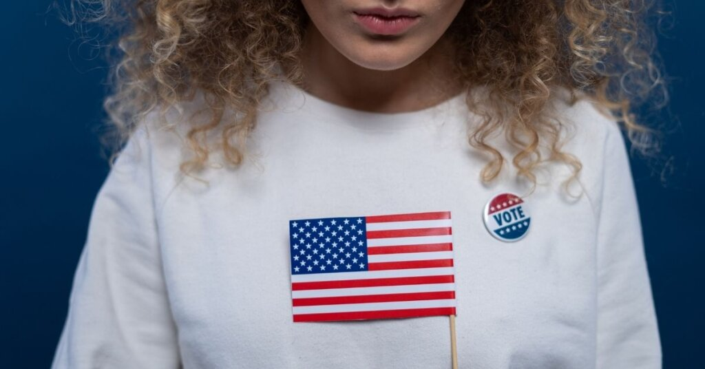 Woman holding a flag wearing a VOTE sticker