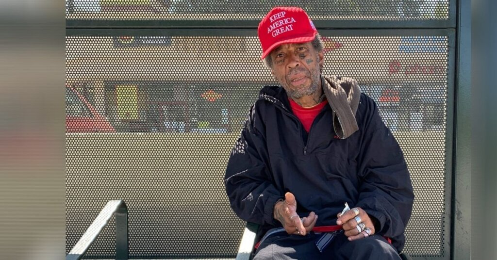 Man wearing a MAGA hat sitting in a busstop