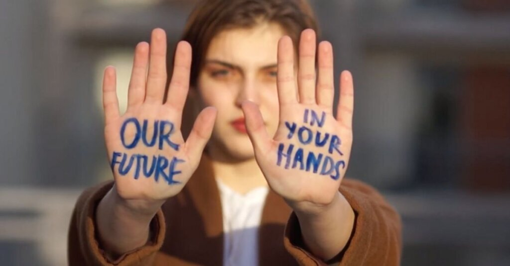 "A girl with ""our future in your hands"" written on her palms"