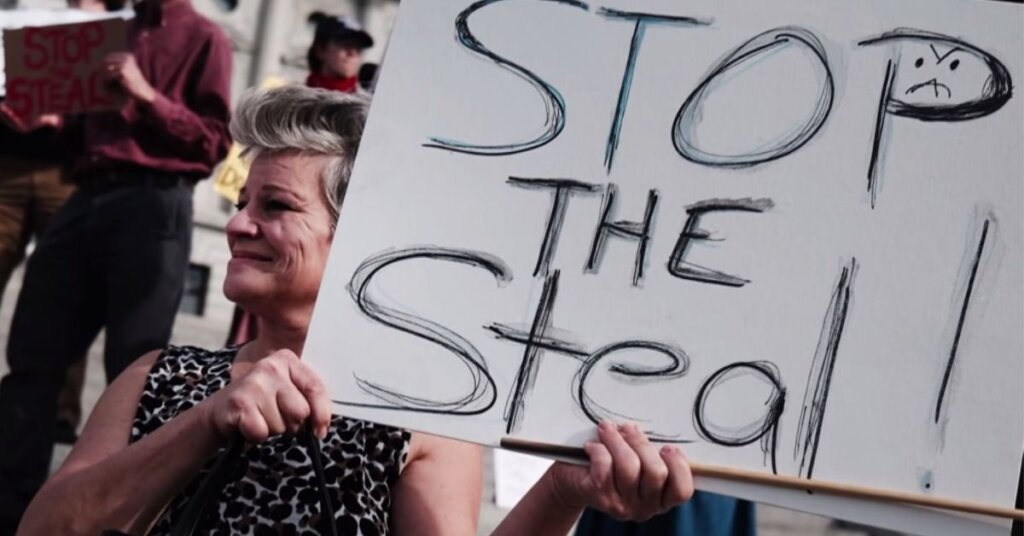 Woman holding 'Stop the steal' sign