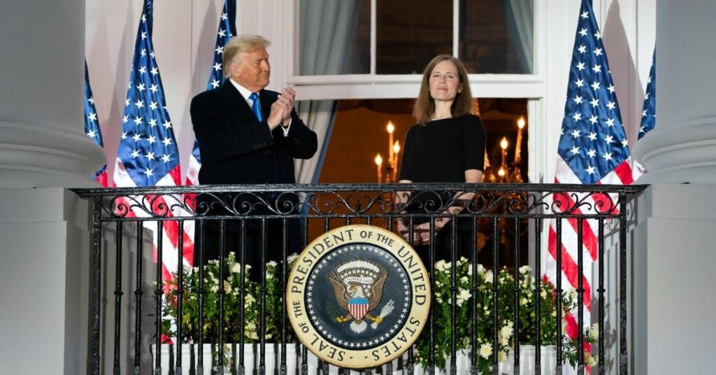 Trump and Amy Coney Barrett standing on a balcony