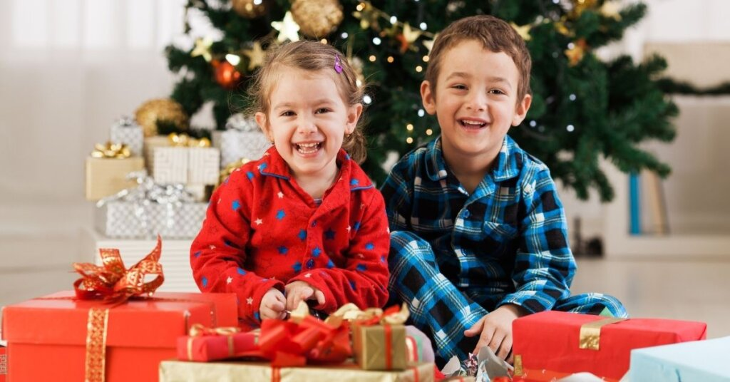 Two children sitting in front of a Christmas tree