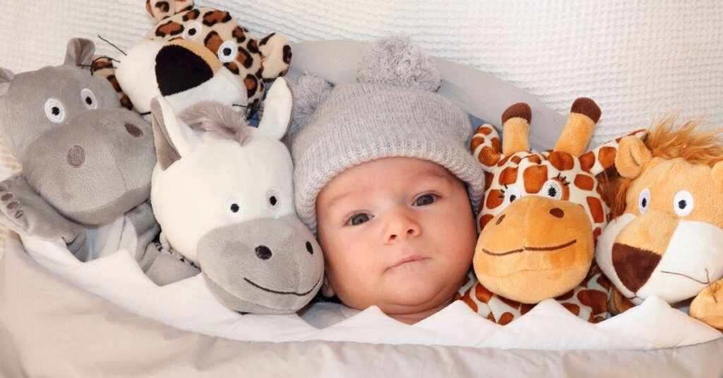 A baby surrounded by stuffed animals