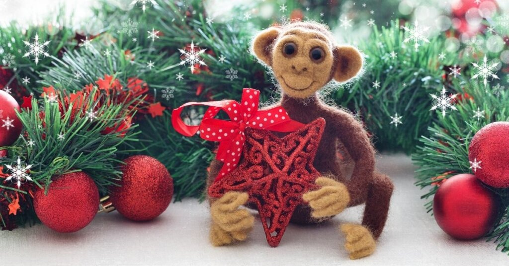 A stuffed monkey surrounded by Christmas decorations