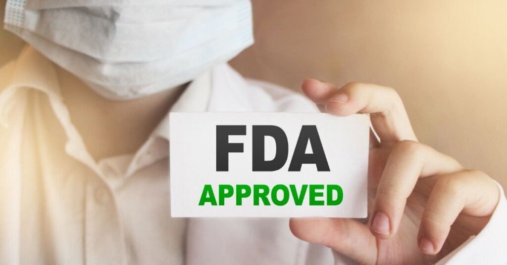 """Person holding a card that says """"FDA approved"""""""