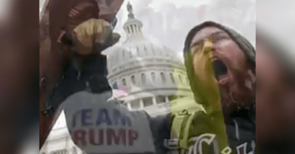 A member of Trump's insurrection screams in front of the US Capitol.