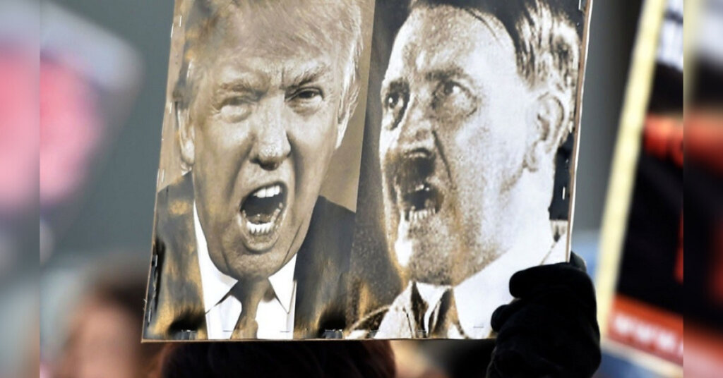 A participant of a Women's March in Helsinki holds up a poster depicting former U.S President Donald Trump and German dictator Adolf Hitler on Jan. 21, 2017.