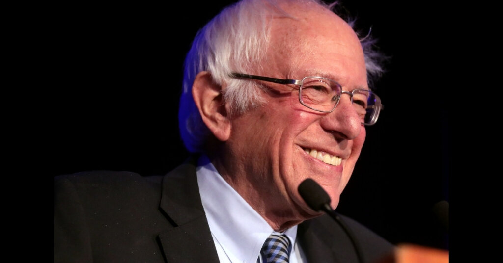 Sanders smiling while standing in front of a microphone