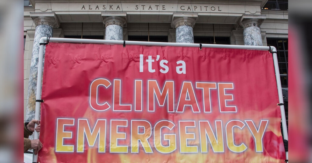 """Descriptive image of sign that reads """"It's a climate emergency"""" in front of the Alaska state capitol"""