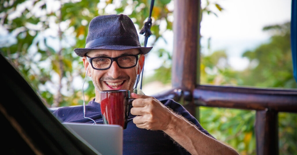 Man wearing a hat and drinking a cup of coffee