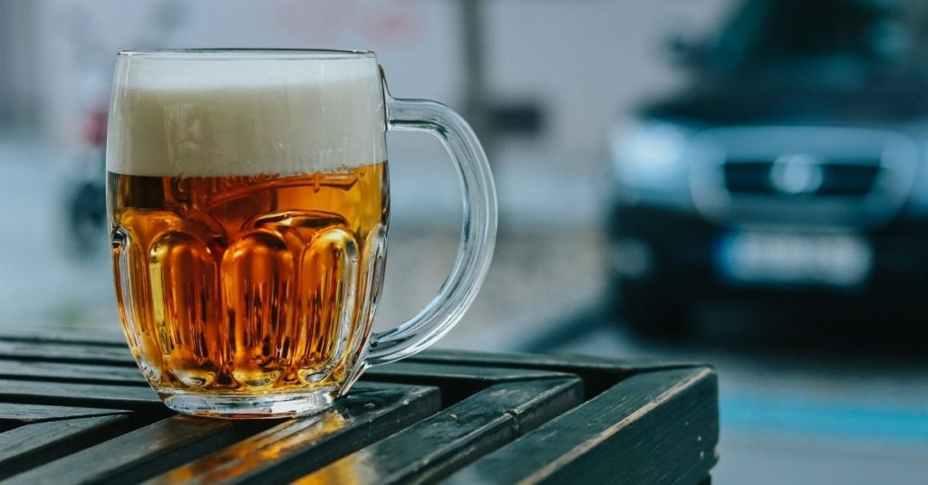 a glass of beer sitting on an outddoor table