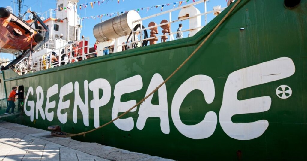 """Ship docked at a harbor with """"Greenpeace"""" written across the hull"""
